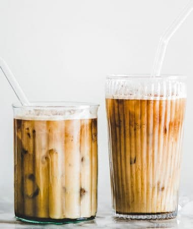 Homemade iced caramel macchiato coffee in glasses with straws on table