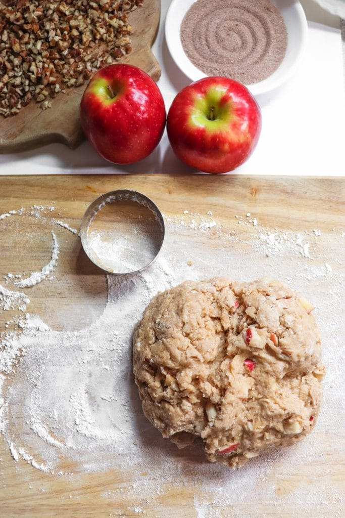 adding chopped apples to the apple cider scones on a cutting board