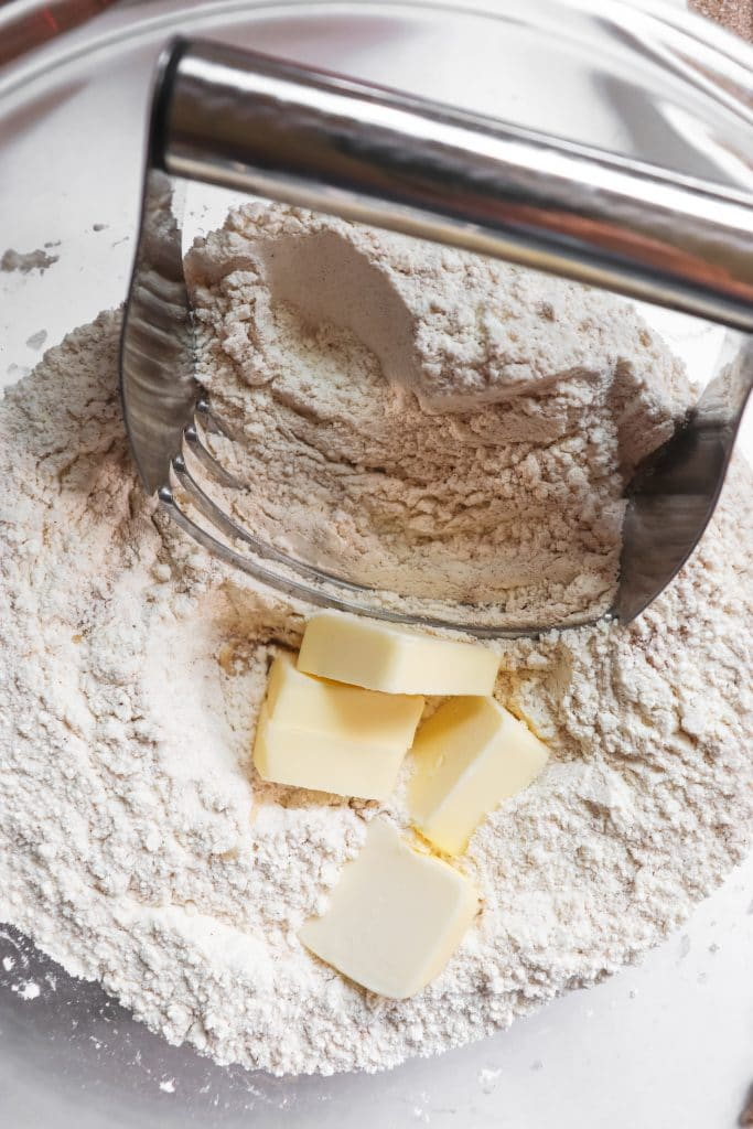 cutting the cold butter intto the flour mixture